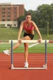 Mulher nova no aquecimento do sutiã dos esportes no obstáculo imagem de stock