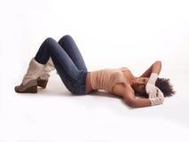 Mulher nova no assoalho em carregadores superiores e em luvas das calças de brim Imagem de Stock