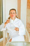 Mulher nova no bathrobe que aprecia a chávena de café Imagem de Stock Royalty Free