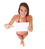 Mulher nova no biquini que aponta no sinal em branco Fotos de Stock