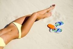Mulher nova no biquini que expore-se ao sol na praia Fotografia de Stock