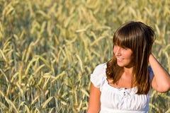 A mulher nova no campo de milho aprecia o por do sol Fotos de Stock Royalty Free