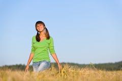 Mulher nova no campo de milho do por do sol Fotos de Stock Royalty Free