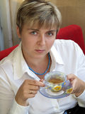 Mulher nova no chá bebendo da colar azul Fotos de Stock