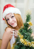 Mulher nova no chapéu de Santa perto da árvore de Natal Imagem de Stock