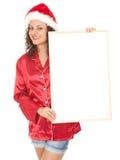 Mulher nova no chapéu vermelho de Santa com poster em branco Fotos de Stock Royalty Free