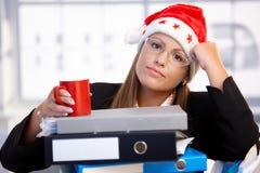 Mulher nova no chapéu de Santa esgotado no escritório Fotos de Stock Royalty Free