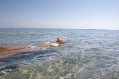Mulher nova no mar calmo. Fotografia de Stock Royalty Free