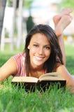 Mulher nova no parque, no livro e na leitura verdes Fotografia de Stock Royalty Free