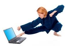 A mulher nova no quimono atende à ioga com portátil fotos de stock royalty free