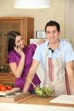 Mulher nova no telefone e no homem novo na cozinha Fotografia de Stock Royalty Free