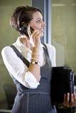 Mulher nova no telefone móvel que está pela porta de vidro Imagens de Stock Royalty Free