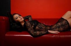 Mulher nova no vestido preto que encontra-se no sofá Foto de Stock