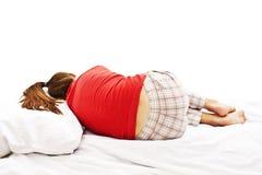 Mulher nova nos pijamas que colocam na cama imagens de stock
