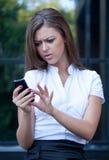 A mulher nova olha no telefone e está irritada Fotografia de Stock Royalty Free