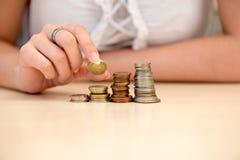 A mulher nova põr moedas sobre moeda-empilha Imagens de Stock