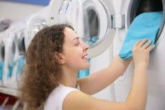 A mulher nova põr o linho na máquina de lavar na loja Fotografia de Stock Royalty Free