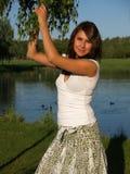 Mulher nova pelo lago com uma árvore fotografia de stock royalty free
