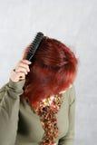 A mulher nova penteia o cabelo Foto de Stock Royalty Free