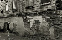 Mulher nova perto da casa arruinada com tijolos Imagem de Stock