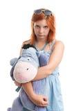 Mulher nova que abraça o brinquedo grande do burro Fotografia de Stock Royalty Free