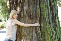 Mulher nova que abraça o grande tronco de árvore imagens de stock