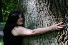 Mulher nova que abraça uma árvore foto de stock royalty free