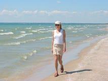 Mulher nova que anda na praia foto de stock