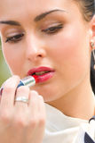 Mulher nova que aplica cosméticos em seus bordos Foto de Stock Royalty Free