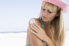 Mulher nova que aplica o produto da proteção do sol imagens de stock royalty free
