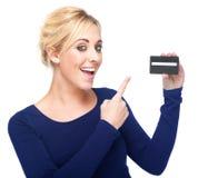 Mulher nova que aponta em um cartão de crédito imagens de stock