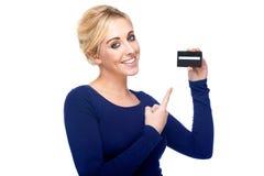 Mulher nova que aponta em um cartão de crédito foto de stock royalty free