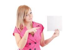 Mulher nova que aponta no cartão em branco em sua mão Fotografia de Stock