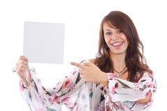 Mulher nova que aponta no cartão em branco em sua mão Imagens de Stock Royalty Free