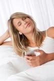 Mulher nova que aprecia a música com botões da orelha Fotografia de Stock