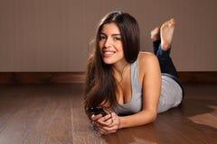 Mulher nova que aprecia a música em seu telefone esperto Fotografia de Stock