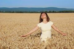 Mulher nova que aprecia no campo de grão Imagem de Stock