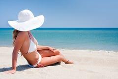 Mulher nova que aprecia o sol em uma praia Imagem de Stock Royalty Free