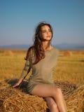 Mulher nova que aprecia a pilha do feno da brisa do verão imagem de stock royalty free