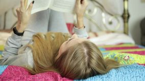 Mulher nova que aprende em casa menina que lê um livro em uma cama video estoque