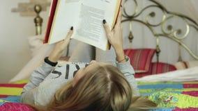 Mulher nova que aprende em casa menina que lê um livro em uma cama filme