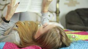 Mulher nova que aprende em casa menina que lê um livro em uma cama vídeos de arquivo