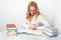 Mulher nova que aprende na tabela com muitos livros Fotos de Stock Royalty Free