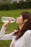Mulher nova que bebe a água mineral Fotografia de Stock Royalty Free