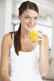 Mulher nova que bebe um vidro do sumo de laranja Fotos de Stock Royalty Free