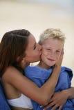 Mulher nova que beija o menino Foto de Stock Royalty Free