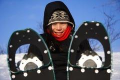 Mulher nova que caminha com sapatas/raquetes da neve foto de stock