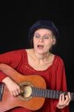 Mulher nova que canta e que joga a guitarra Imagens de Stock Royalty Free