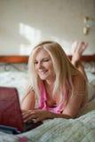 Mulher nova que chating em linha com o portátil em sua cama Imagem de Stock Royalty Free