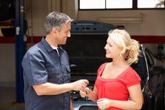 Mulher nova que coleta o carro da loja de reparo Fotos de Stock Royalty Free
